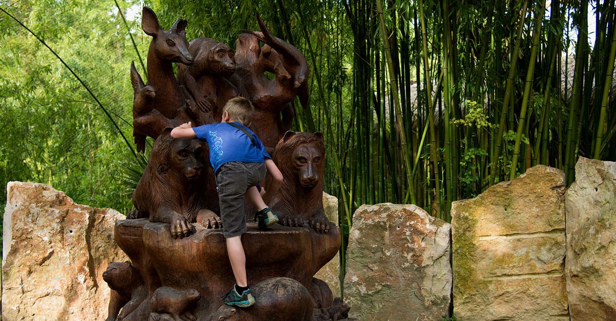 enfant qui grimpe sur une sculpture